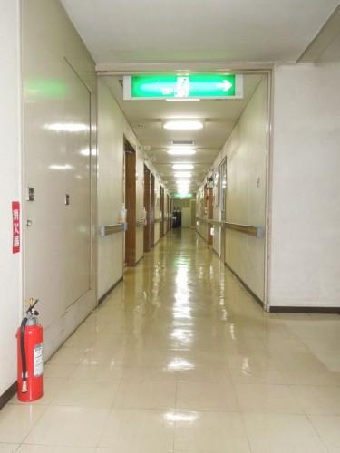 当診療所2階の病棟廊下。左に防火扉。上が避難誘導灯。右が避難階段。