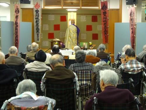 豊寿苑内での祈祷の様子。奥は未年を迎えたご利用者名で紅白の布を奉納。
