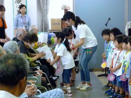子どもたちからお年寄りへ花束のプレゼント